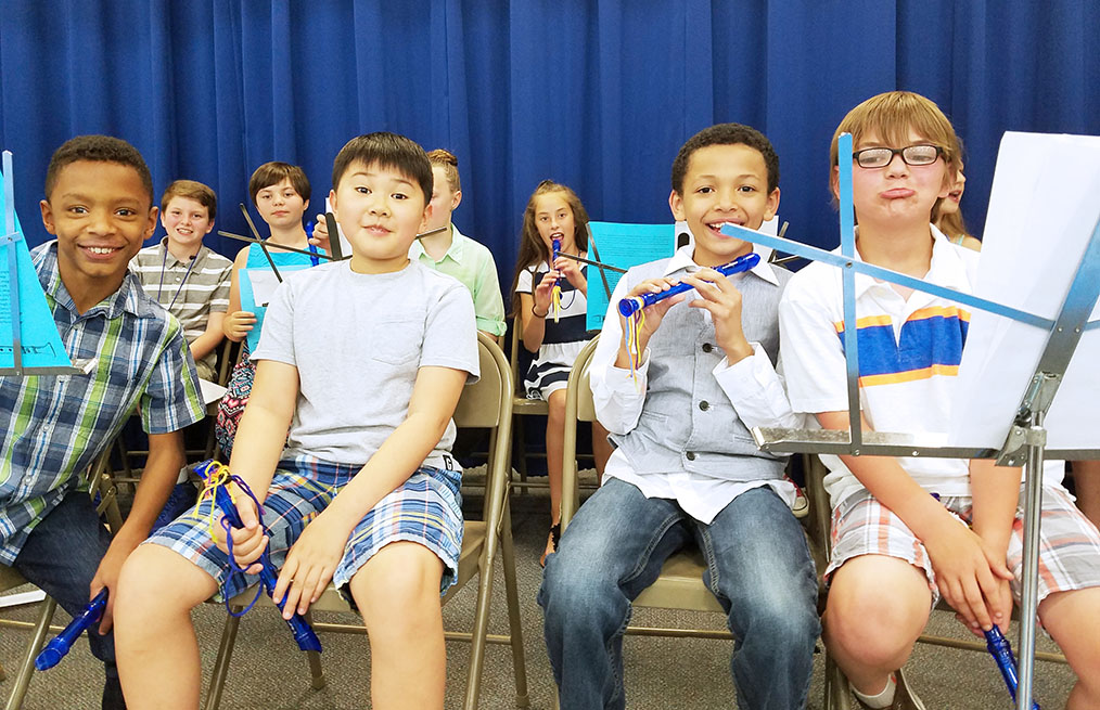 4 boys sitting in chairs holding instruments.