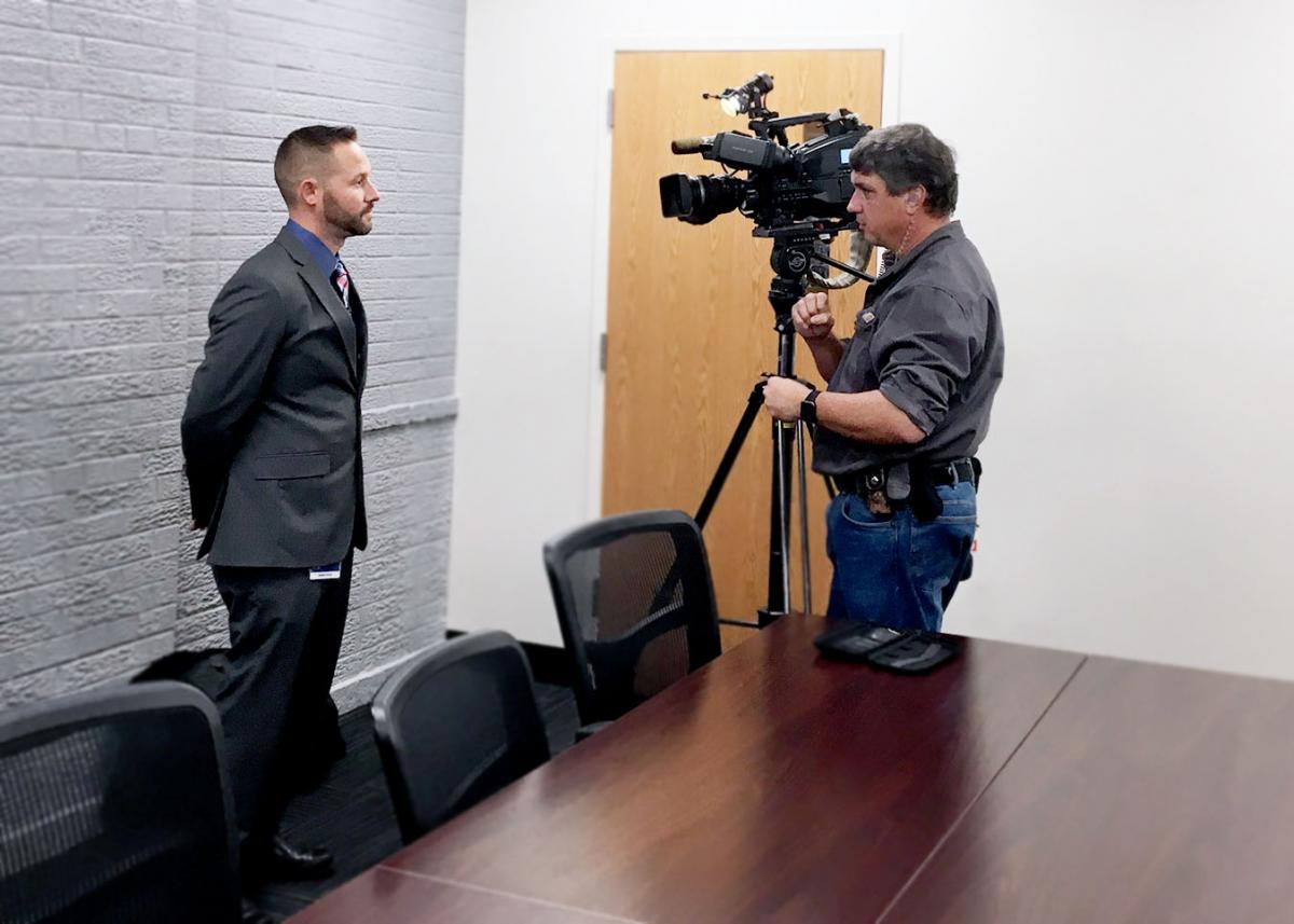 Man standing in front of video camera. Second man standing next to video camera