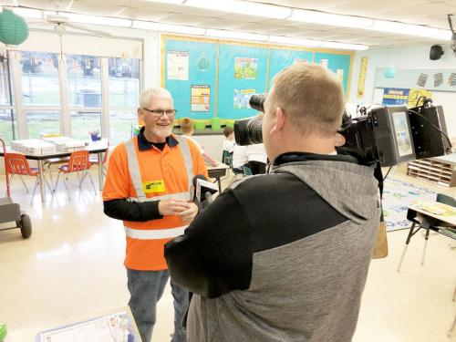Adult male smiling at reporter. Male reporter back to camera. Brooklyn STEM Adademy chosen by JB Hunt Transport for Adopt-A-Class.